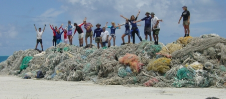 People standing on top of a large pile of derelict nets. (Photo Credit: NOAA)