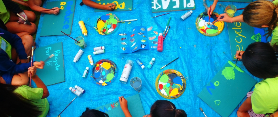 Students participating in an educational marine debris art activity. The students are in a circle around a plastic tarp, painting marine debris messages on pieces of wood.