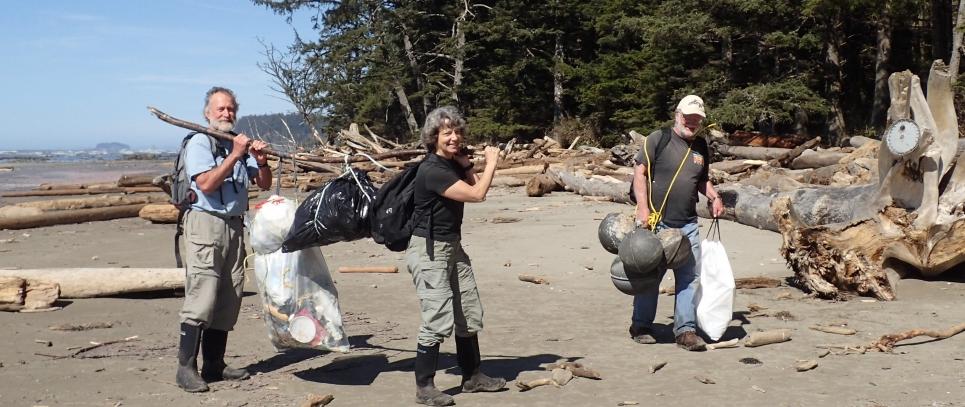 Three people carrying marine debris off a beach.