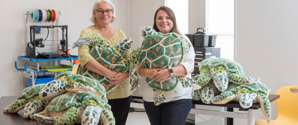 Two women holding stuffed turtles