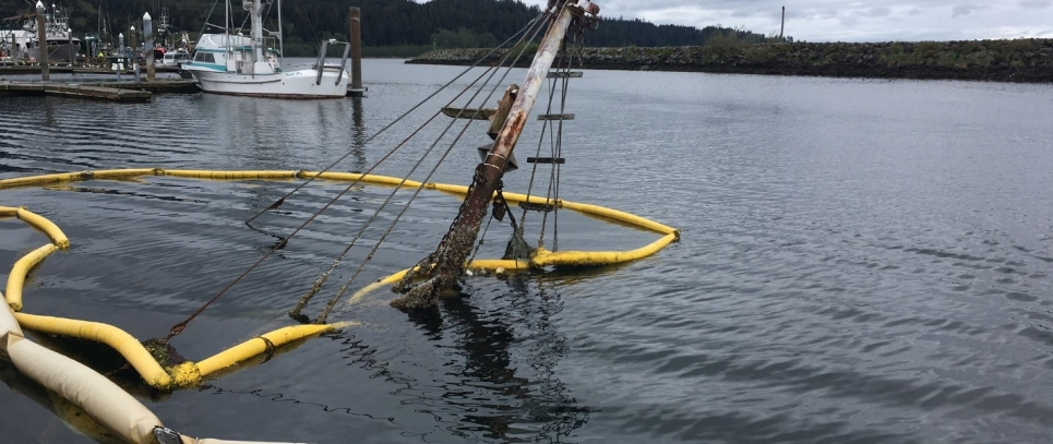 The mast of a sunken vessel protrudes out of the water at the Makah Marina in Neah Bay.