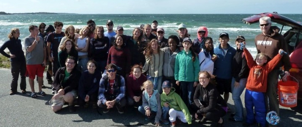 A cleanup group posing in front of a beach.