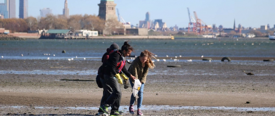 Kids picking up debris on a NYC beach.