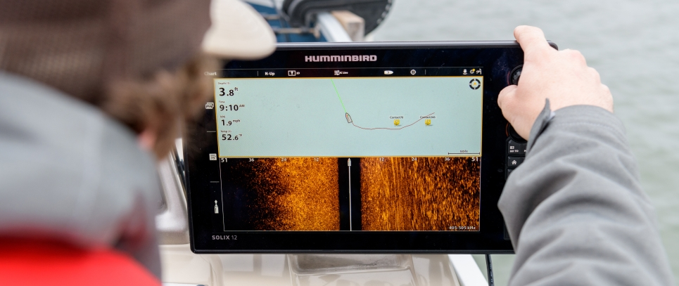 A person on a boat looking at a tablet screen that shows the location of crab pots.