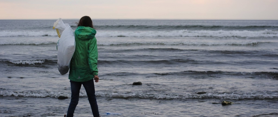 A volunteer holding a bag of collected debris and walking through the water on a beach.