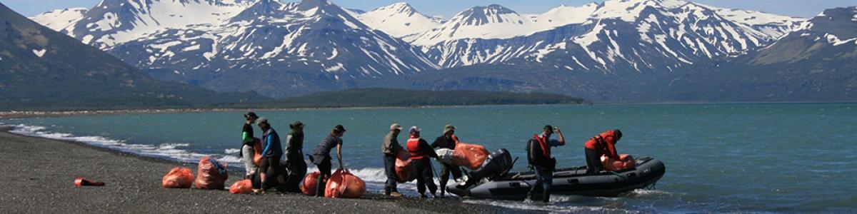 Volunteers loading debris into a boat on a remote Alaskan shoreline.