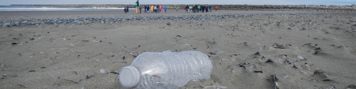 Kids on the beach with plastic bottle trash in the foreground.