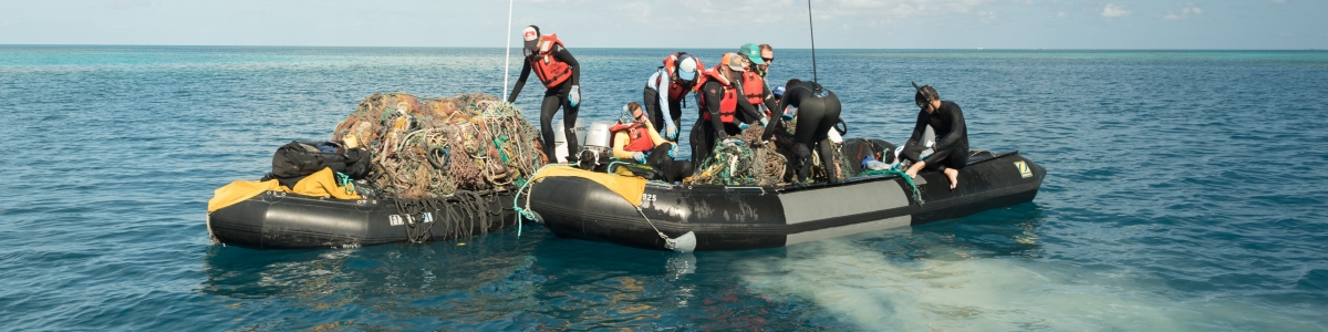 People haul a derelict fishing net into a boat.