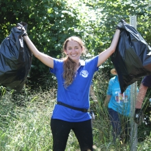 A volunteer smiling and holding up two bags of collected debris.