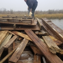 A person bends down to pick up some lumber in a pile that was created by a hurricane in North Carolina.