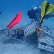 Divers attach lift bags to remove marine debris, including lawn chairs and galvanized metal, from Coki Beach, U.S. Virgin Islands.