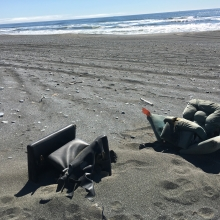 Two armchairs on a beach.