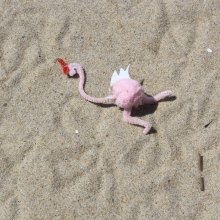 Pink flamingo decoration made out of pipe cleaners on a beach.