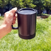 A reusable mug is held up by a hand in front of grass.