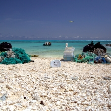 Two piles of marine debris collected from separate 300-m shoreline segments are staged to be loaded onto the small boat. (NOAA PIFSC Coral Reef Ecosystem Program)