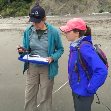 Two people looking at a clipboard and GPS tracker on a beach.