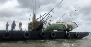 Abandoned boats loaded on a salvage vessel.