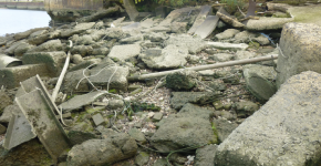 Ropes and other debris scattered along a rocky shore.