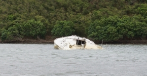 A derelict vessel partially-submerged in water.