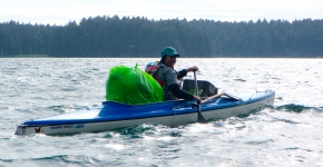 A volunteer in a kayak with a bag of debris.