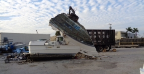 Derelict vessel being crushed at a landfill yard.