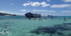 A derelict vessel in the background while several people swim in a beautiful lagoon.