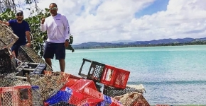 Two men stand on a beach next to a pile of collected crab traps.
