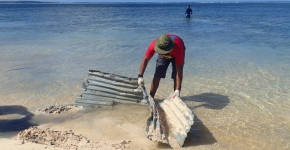 A volunteer removing corrugated roofing tin from an ocean shore.