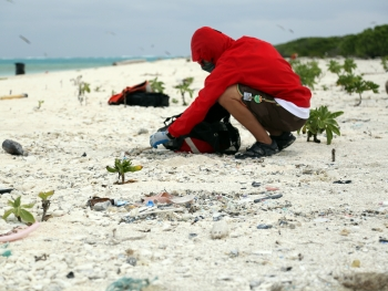 A Marine Debris team member picks out debris from the wrack-line where debris accumulates. (Photo credit: NOAA CREP)