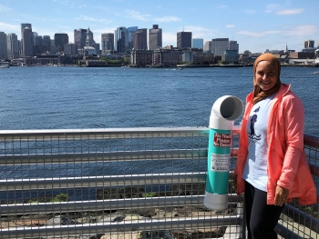 A person stands next to a monofilament recycling bin that is located near the water.