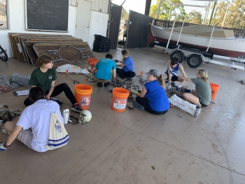 Eckerd College students sorting through debris collected during a beach clean-up.