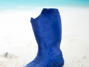 A rubber boot washed up on the sandy shores of North Beach, Sand Island, Midway Atoll.