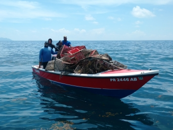 A dive crew transporting derelict fishing gear back to shore after a removal expedition.