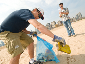 A volunteer cleaning up debris along a beach.