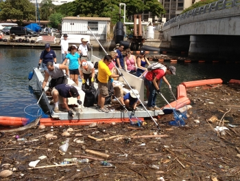 ICC volunteers scoop marine debris out of a trash boom in Honolulu.
