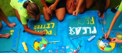 Kids painting signs on a tarp.
