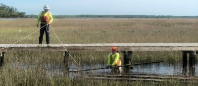 Two people work to remove construction debris from a marsh after a hurricane in Georgia.