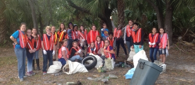 A class in Georgia conducts a cleanup as they stand for a group picture and smile.