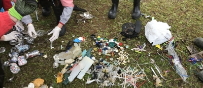 People organize marine debris into piles on the grass.