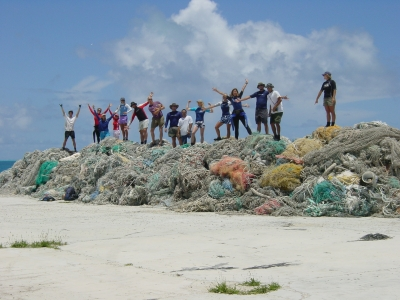 NOAA divers stand on a pile of nets they removed in Hawaii.
