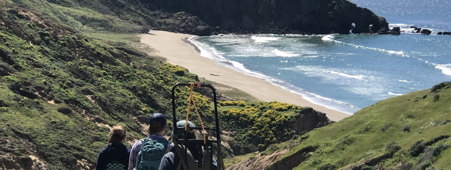 Three people hiking together through hills overlooking an ocean beach.
