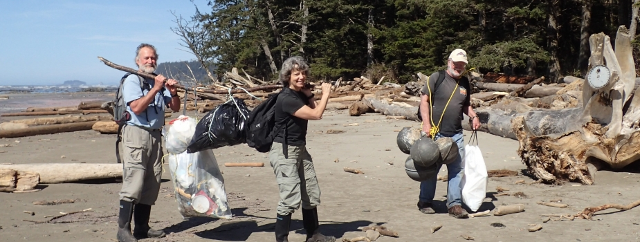 Three people carrying marine debris off a beach.
