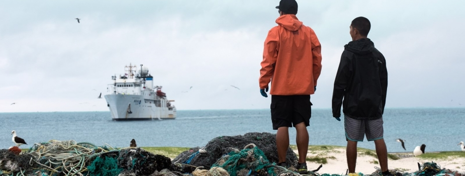 Two team members stand next to a pile of collected derelict fishing nets during the 2016 removal mission.