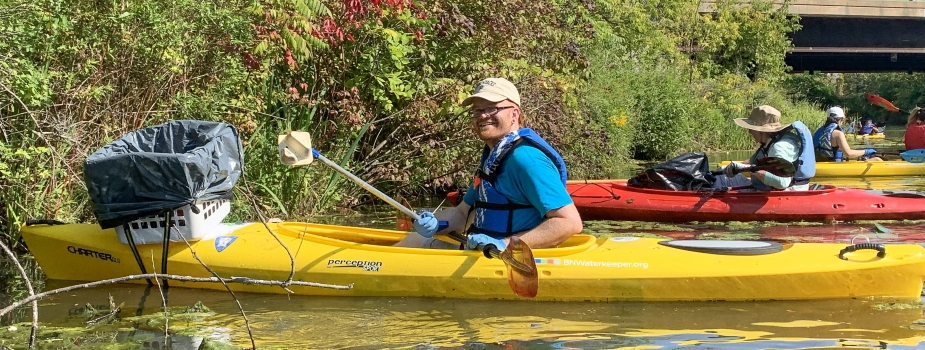 A person paddling a kayak smiles for a picture. A laundry basket lined with a black garbage bag has been attached to the front of the kayak.