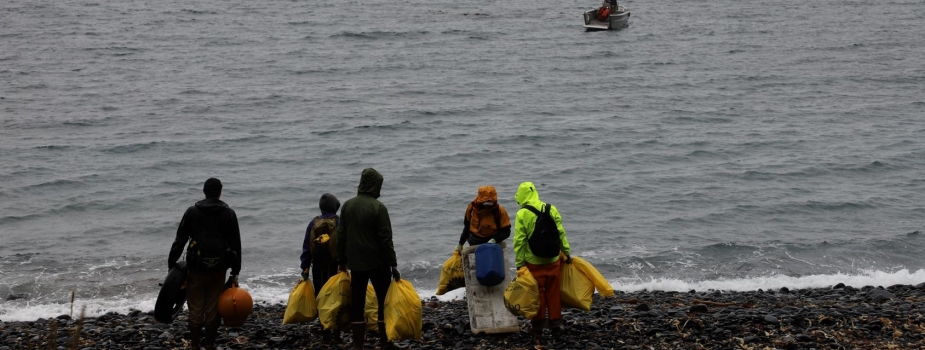 A crew of people holding filled garbage bags standing at the shoreline and watching an incoming small boat.