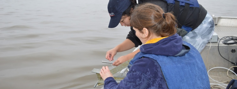 Two people taking a water sample from a boat.