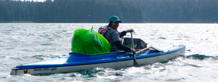 A volunteer in a kayak with a bag of debris.