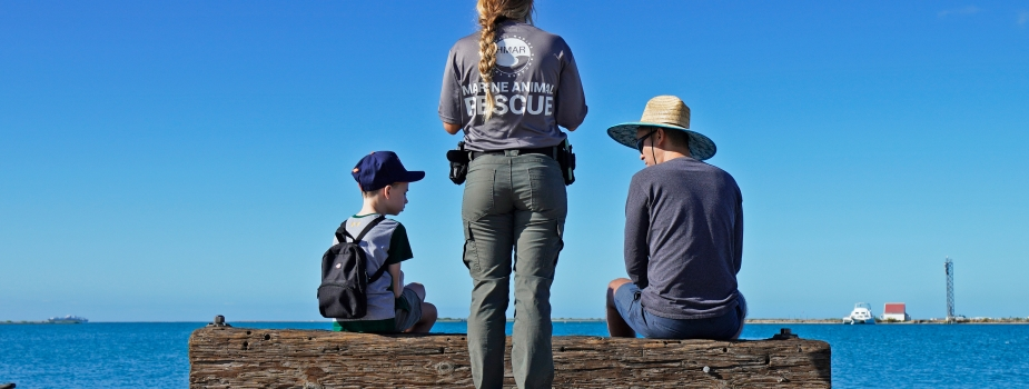 A Hawaii Marine Animal Response staff member speaking to a child and adult sitting on timber overlooking the ocean.