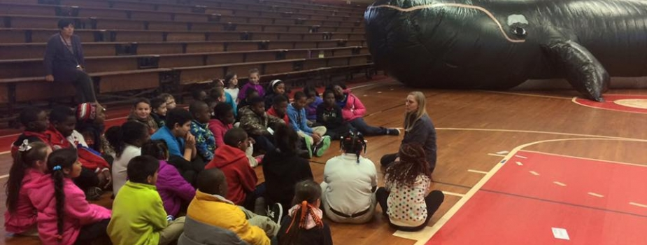 Students sit on the floor in discussion with the inflatable whale classroom in the background.