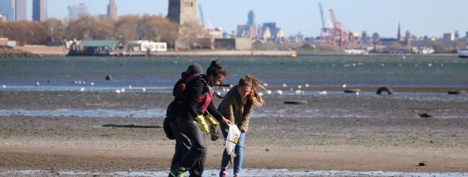 Kids picking up debris on a NYC beach.